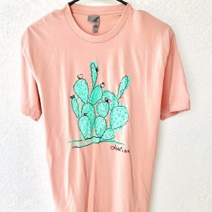 A photograph of the Cactus T-Shirt hanging against a plain background