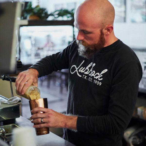 A photograph of a male model pouring coffee while wearing the Lubbock 1909 Long-Sleeve Shirt