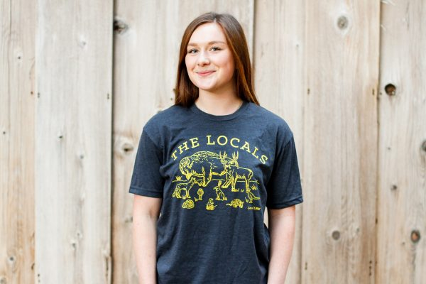 Photograph of a female model wearing the navy blue Locals T-Shirt against a wood backdrop