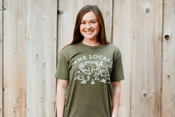 A photograph of a female model wearing the olive green Locals T-Shirt against a wood backdrop